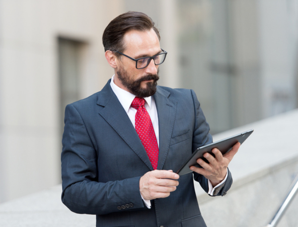 Man in a business suit looking at a tablet.